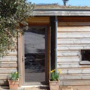 La terre de la toiture végétalisée est arrêtée par une remontée d'étanchéité derrière une gouttière standard